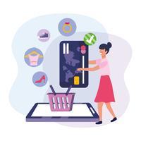 Mulher com smartphone e cartão de crédito e cesta com objetos de varejo