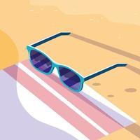 Óculos sobre a toalha no design da praia
