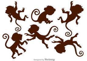 Silhuetas de macaco marrom vetor