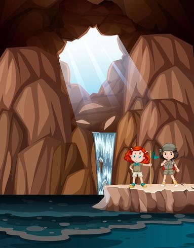 Ragazze che esplorano una grotta con cascata vettore