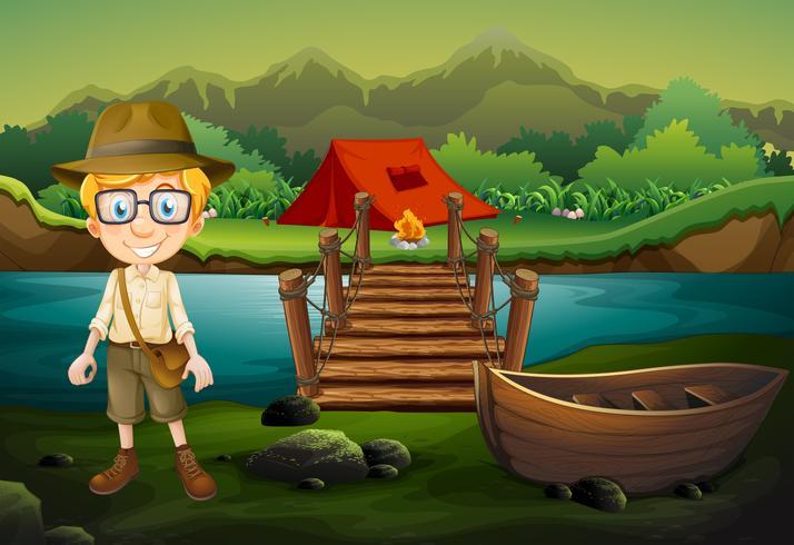 Un boy scout in campeggio nella foresta vettore
