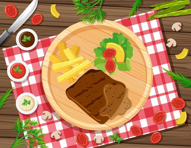 Bistecca con patatine fritte e insalata sul piatto vettore