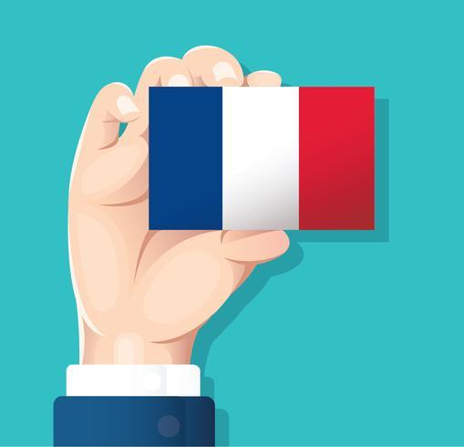 mano che tiene la carta della bandiera della Francia con sfondo blu vettore