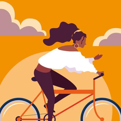 giovane donna afro equitazione bici con cielo arancione vettore