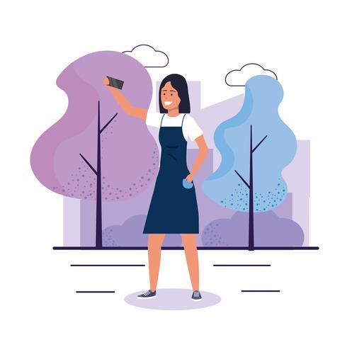 Giovane donna con lo smartphone che prende selfie in parco vettore