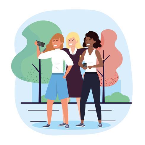 Gruppo di diverse donne che prendono selfie nel parco vettore