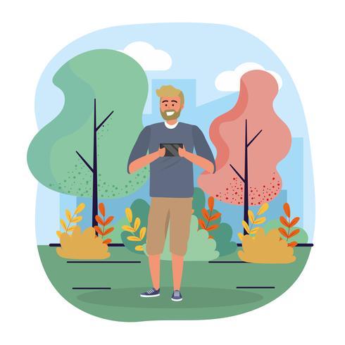 Uomo con la barba che esamina smartphone in parco vettore