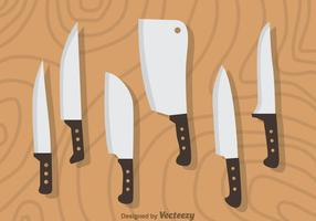 Set di coltelli su legno vettoriale
