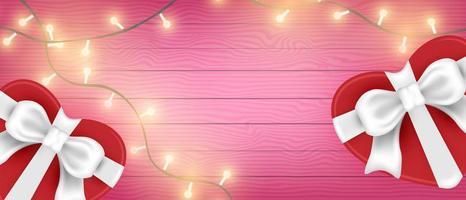 scatole regalo a forma di cuore di San Valentino e luci su legno