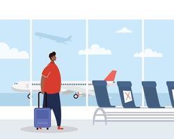 uomo con maschera facciale e valigia in aeroporto