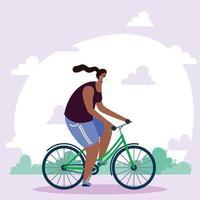 giovane donna africana che indossa maschera medica in bicicletta vettore