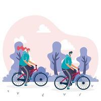 giovane coppia che indossa maschere mediche in bicicletta