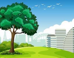 parco scena all'aperto con un albero e molti edifici in background vettore