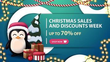 settimana di saldi e sconti natalizi, fino a 70, striscione blu con anelli decorativi bianchi, ghirlande e pinguino in cappello di babbo natale con regali