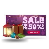 saldi natalizi, sconti fino a 50, banner sconto 3d viola con regalo, lanterna vintage, ramo di un albero di natale con un cono e una palla di natale vettore