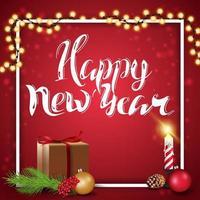 felice anno nuovo, saluto cartellino rosso con regalo, candela, palla di Natale e ramo di un albero di Natale vettore
