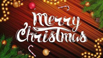 buon Natale, bella cartolina con scritte, ghirlanda, ramo di un albero di Natale e bastoncino di zucchero su fondo in legno vettore