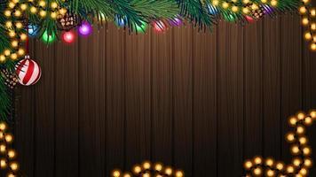 parete in legno con ramo di un albero di natale e decorazioni natalizie. sfondo per le tue arti con spazio di copia vettore