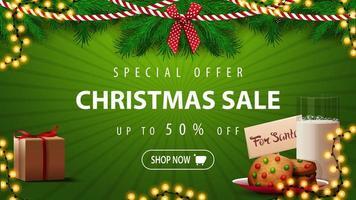 offerta speciale, saldi natalizi, sconti fino a 50, bellissimo banner sconto verde con rami di albero di natale, ghirlande e biscotti con un bicchiere di latte per babbo natale vettore