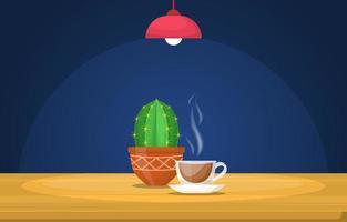 una tazza di tè caldo e un cactus su un tavolo sotto una lampada vettore
