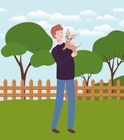giovane uomo che alza mascotte cane carino nel campo vettore