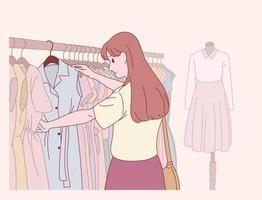una donna sceglie i vestiti in un negozio di abbigliamento. vettore