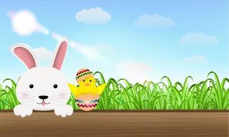 uovo di Pasqua del pulcino del coniglietto sulla tavola di legno vettore