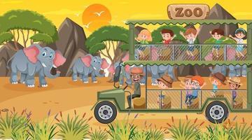 zoo al tramonto con molti bambini che guardano il gruppo di elefanti vettore