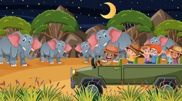 safari in scena notturna con molti bambini che guardano un gruppo di elefanti vettore