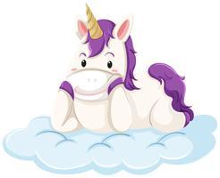 Un unicorno si sdraia sulla nuvola vettore