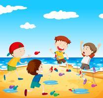 I bambini felici giocano a pallone combattono in spiaggia