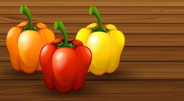 Tre peperone dolce differente su fondo di legno