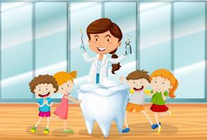 Dentista e bambini felici vettore