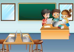 Tre bambini che lavorano al computer in classe vettore