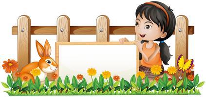 Una ragazza che tiene un bordo bianco con un coniglio dentro il recinto di legno vettore