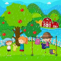 Scena del giardino con i bambini facendo il bucato sotto la pioggia