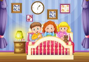 Tre bambini nel letto rosa nelle ore notturne