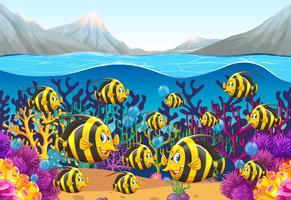 Scena con pesci che nuotano sotto il mare vettore