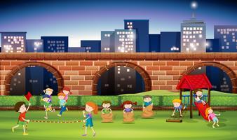 Bambini che giocano nel parco di notte vettore