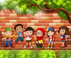 Bambini provenienti da diversi paesi in piedi sotto l'albero vettore