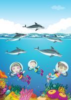 Delfini e bambini che nuotano sotto il mare
