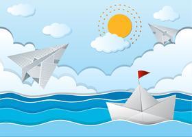 Scena dell'oceano con aeroplano di carta e barca