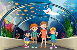 Bambini che visitano un acquario pieno di pesci vettore