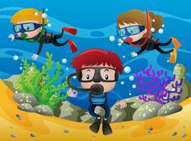 Tre bambini che si tuffano sotto l'oceano