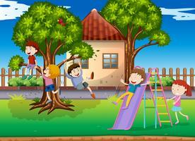 Bambini che giocano a scivolo nel parco giochi vettore