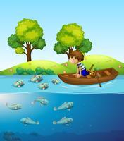 Un ragazzo sulla barca a guardare il pesce vettore