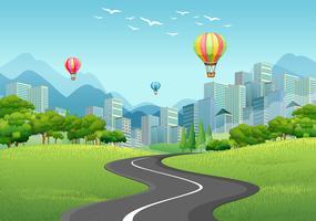 Città con edifici alti e palloncini vettore