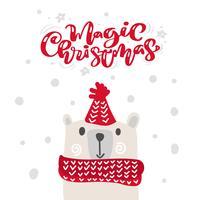 Magia Natale calligrafia lettering testo. Cartolina d'auguri scandinava di natale con l'illustrazione disegnata a mano di vettore dell'orso sveglio con il cappello e la sciarpa rossi. Oggetti isolati