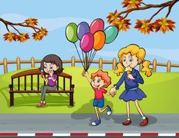 Due ragazze con un bambino che tiene un pallone nel parco vettore