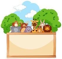 Tavola di legno con simpatici animali sullo sfondo